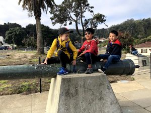 Boys sitting on a historical cannon