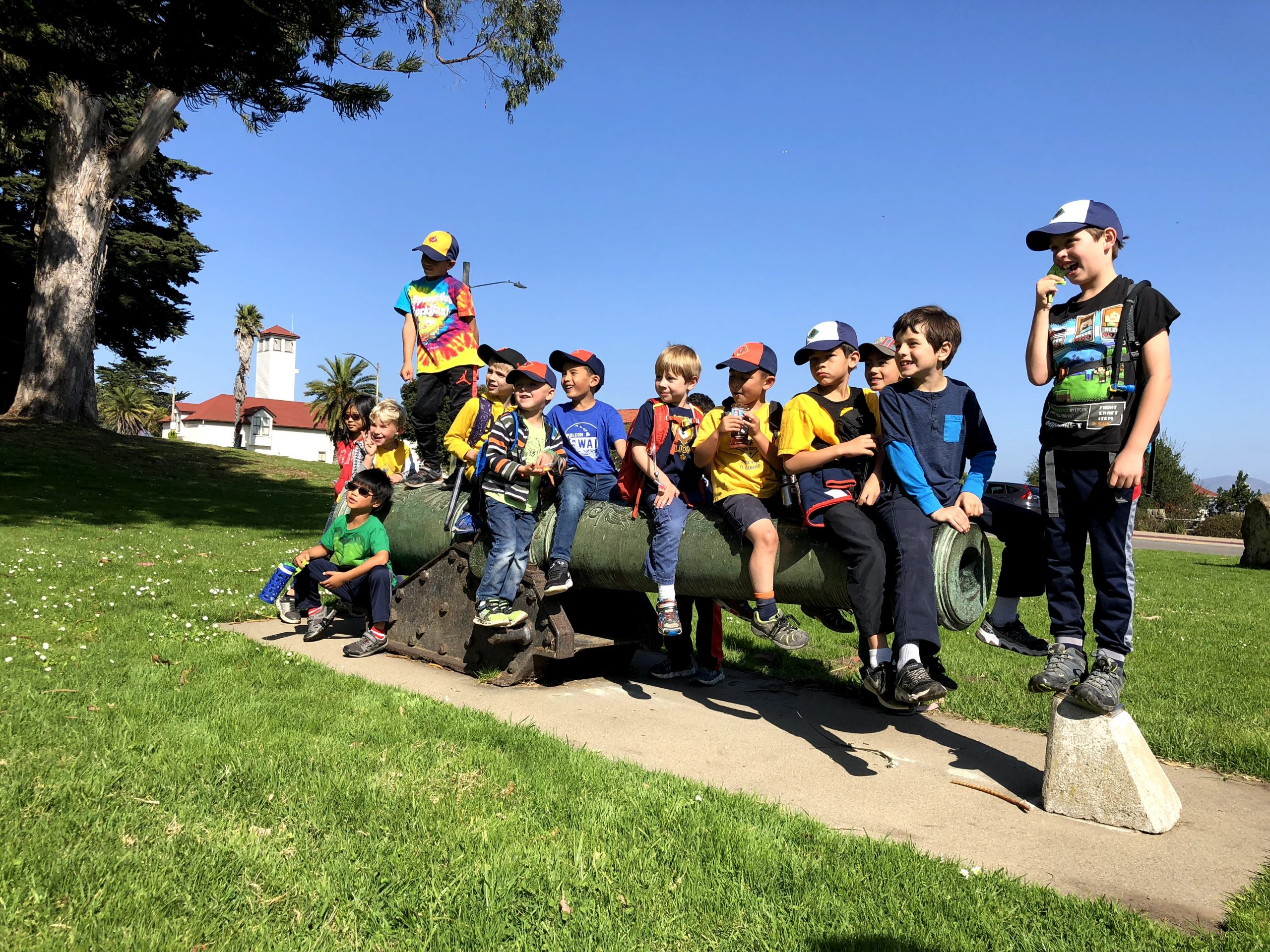 Group photo of cub scouts sitting on a historical cannon at the Presidio